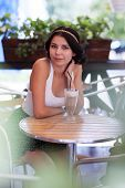 Attractive Brunette Girl In A Cafe Outdoors
