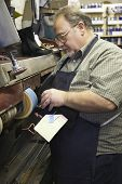 Side view of a male shoemaker at work in traditional workshop