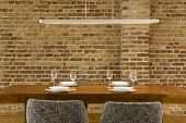 stock photo of koln  - View of wineglasses and plates on dining table against brick wall in modern house - JPG