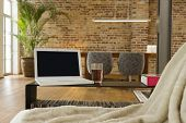 image of koln  - View of a laptop and drink with dining area in the background at modern house - JPG