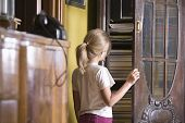 Rear view of a young girl opening cupboard door