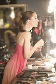 Side view of a female fashion model in pink slip looking at dressing room mirror