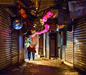 JIUFEN, TAIWAN - JANUARY 17: A couple pass through a shoplined alleyway after hours January 17, 2013
