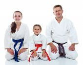 Dad with his daughters in kimono sitting in a ritual pose Karate