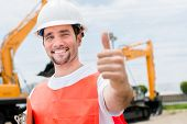 Happy contractor at a building site with thumbs up