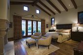stock photo of hacienda  - View of a spacious bedroom with seating area and beamed ceiling at home - JPG