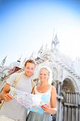 Travel couple reading map on in Venice, Italy on Piazza San Marco in front of Saint Mark's Basilica. Happy young couple on travel vacation in Europe. Happy woman and man in love traveling together.