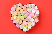High angle view of a heart shaped box filled with Valentine's Day Candies. The box in the middle of a red background. The heart shaped candy is blank and ready for your message.