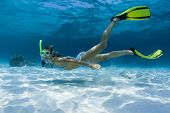 Young lady swimming underwater on a breath hold in a tropical sea with yellow fins
