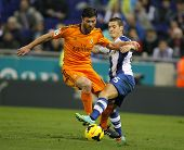 BARCELONA - JAN, 12: Xabi Alonso of Real Madrid vies with Gabriel Torje of RCD Espanyol during the Spanish League match at the Estadi Cornella on January 12, 2014 in Barcelona, Spain