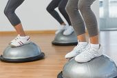 stock photo of step aerobics  - Closeup low section of fit people performing step aerobics exercise in gym - JPG