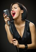 Half-length portrait of female musician with closed eyes wearing black evening dress and keeping microphone on grey background. Concept of music and retro fashion