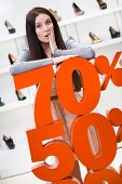 Woman showing the percentage of sales on footwear in the shopping center against the window case wit