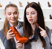 Salesperson offers high heeled shoes for the female customer in the shopping center