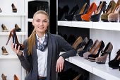 Woman with shoe in hand chooses high heeled shoes looking at the shelves with numerous pumps