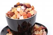 Closeup of dried fruits in a black cup
