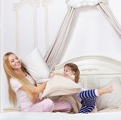 picture of pillow-fight  - Cheerful family having pillow fight in a bedroom - JPG