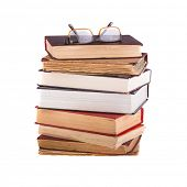 A pile of different books and glasses, isolated on white background.