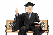 Mature man in graduation gown seated on wooden bench holding a book and giving thumb up isolated on