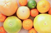 foto of clementine-orange  - Background of assorted citrus fruit with lemon lime orange tangerine clementine and grapefruit close up view from above on a wooden background - JPG