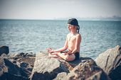 Young boy practising yoga on beach