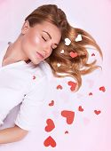 Romantic fashion model lying down on the floor with closed eyes decorated with many little red heart