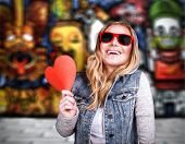 Funky teen girl in love, having fun outdoors, holding in hands  red heart as symbol of adolescents a