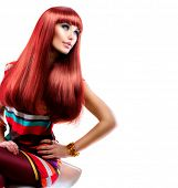 Fashion Sexy Model Girl Sitting on Chair. Beauty Woman isolated on White. Woman in colorful Dress with Long healthy red hair. Fringe hairstyle. Smoky eyes make up