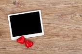 Blank instant photo and red candy hearts on wooden table background