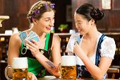 In Pub - friends in Tracht, Dirndl and Lederhosen drinking a fresh beer in Bavaria, Germany playing