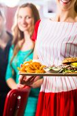 Friends or couple eating fast food in American fast food diner, the waitress wearing a short costume serving a meal