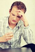 Disappointed, sad man sitting with alcohol drink (glass of whiskey). Young and lonely depressed man wearing bright, plaid shirt with his head down.