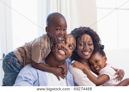 Happy family posing on the couch together at home in the living room poster
