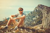 Young Man Relaxing Outdoor With Mountains On Background Summer Vacations And Lifestyle Hiking Concep