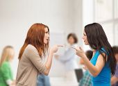bullying, education, friendship and people concept - two teenagers having a fight at school