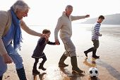 Grandparents With Grandchildren Playing Football On Beach