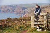 Boy With Dog Walking Along Coastal Path
