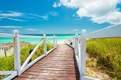 Wodden walkway leading to a beautiful tropical beach in Cuba