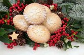 Christmas mince pie cakes with holly, mistletoe and snow covered fir.