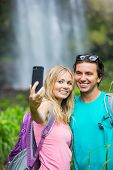 Couple having fun together outdoors. Taking self portrait with camera phone after hiking to incredib