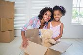 Cute daughter unpacking her teddy bear with mother in their new home