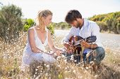 stock photo of serenade  - Handsome man serenading his girlfriend with guitar on a sunny day - JPG