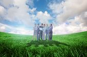 Business team looking at camera against green field under blue sky