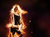 image of guitar  - Portrait of burning young attractive blond woman playing on electric fire guitar - JPG