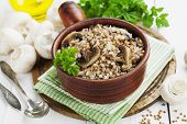 picture of porridge  - Buckwheat porridge with mushrooms in a ceramic pot on the table - JPG