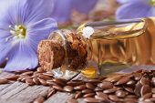 stock photo of flax seed oil  - flowers and flax seed oil in glass bottle on wooden background horizontal