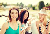 summer holidays, vacation and celebration concept - smiling girls with champagne glasses