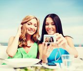 summer holidays, vacation and technology - girls taking photo with digital camera in cafe on the bea