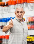 Portrait of confident senior male customer showing thumbs up sign in hardware shop
