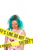 Female zombie standing behind sheriff's DO NOT CROSS tape, isolated on white